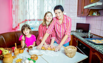 Mom teaching her two daughters cooking on the kitchen