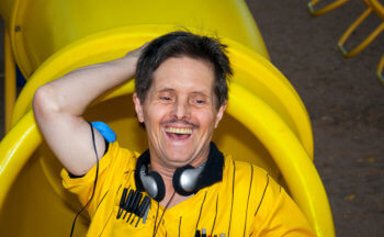 Man With Downs Syndrome Laughs and Plays on a Playground Slide