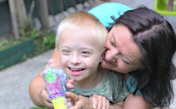 Mother and son with down syndrome smiling