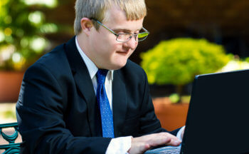boy wearing suit busy with laptop